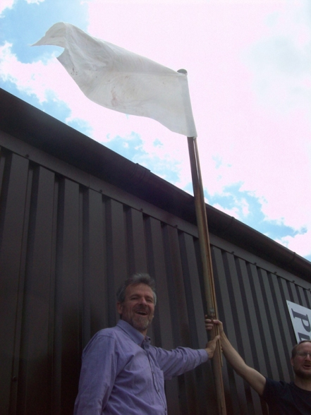 Michael Cahn and Robert Good hoist a flag