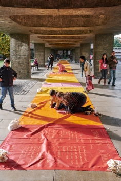 Visitors to the ALL Day of Performances writing on Elisa Vladilo's tarpaulin 'Rhyme of Origin' at the CU Sidgwick Site